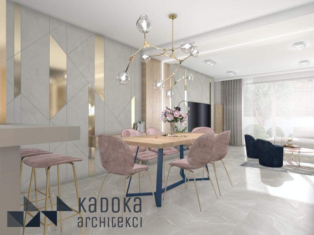 Jadalnia ze złotymi akcentami oraz różowymi krzesłami.