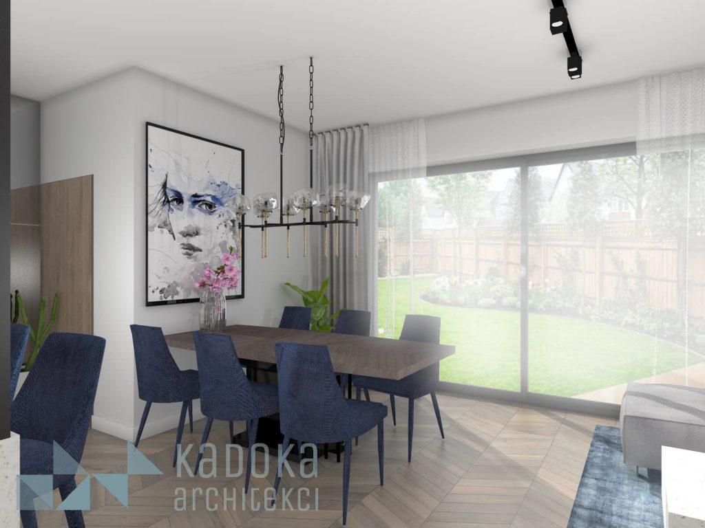 Nowoczesny salon z drewnią podłogą w jodełkę węgierską, drewnianym stołem oraz granatowymi krzesłami.